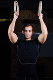 Portrait of young fit muscular man using gymnastic rings royalty free stock image
