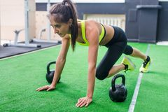 Portrait of young fit woman doing abs and legs fitness exercises in gym stock image