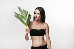 Portrait of young fit woman holding leek Royalty Free Stock Photo