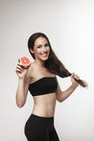 Portrait of young fit woman holding pink grapefruit Stock Photo