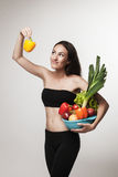 Portrait of young fit woman holding vegetables Royalty Free Stock Images