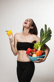 Portrait of young fit woman holding vegetables Stock Photos