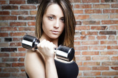 Portrait of Young fit woman lifting dumbbells Stock Photos