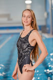 Portrait of a young fit woman looking at camera. Competitive female swimmer in swimming pool posing Royalty Free Stock Image