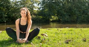 Portrait of young fit woman sitting on the grass Stock Photography