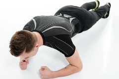 Portrait of a young fitness man doing plank exercise royalty free stock photo