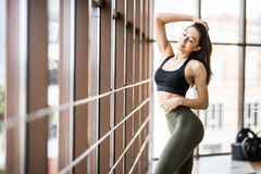 Portrait of young fitness slim woman standing near panoramic window in gym hall stock photos