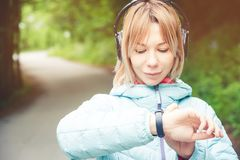 Portrait Young fitness woman looking at her smart watch while taking a break from sports training. Sportswoman checking. Pulse on fitness smart watch device in Royalty Free Stock Photos