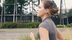 Portrait young fitness woman running at morning jog on summer street