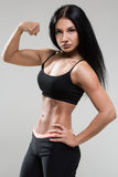 Portrait of young fitness woman shows biceps Stock Photos
