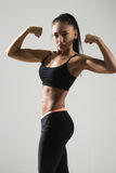 Portrait of young fitness woman shows biceps Royalty Free Stock Images