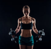 Portrait of a young fitness woman in sportswear doing workout with dumbbells on black background. Tanned athletic girl. A gre Stock Photos