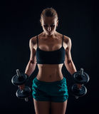 Portrait of a young fitness woman in sportswear doing workout with dumbbells on black background. Tanned athletic girl. Royalty Free Stock Photo