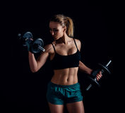 Portrait of a young fitness woman in sportswear doing workout with dumbbells on black background. Tanned sexy athletic girl. Stock Photos