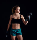 Portrait of a young fitness woman in sportswear doing workout with dumbbells on black background. Tanned sexy athletic girl. Stock Image
