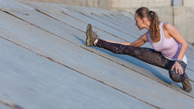 Portrait of a young fitness woman stretching outdoors Royalty Free Stock Images