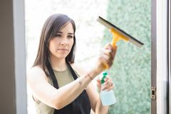 Adorable young woman cleaning glass window with squeegee. Portrait of a young focused latin woman maid cleaning glass window with spray and wiper Royalty Free Stock Image