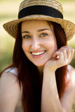 Portrait of young foxy lady in garden. Close up view of beautiful woman in straw hat, holding her hand close to chin Royalty Free Stock Images