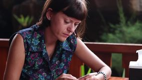 Portrait of a Young freelancer woman using a smartphone, serious, working, busy, nervous, stress, Cafe in Bali island. Young woman using a smartphone, bites her stock video footage