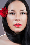 Portrait of young fresh beautiful healthy woman. Red flower Stock Image