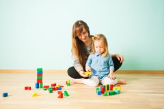 Portrait of teacher and pupil at preschool. Portrait of young fresh teacher and cute girl her pupil learning colours at preschool. Teacher assists young girl to royalty free stock image