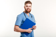 Portrait of a young friendly doctor or nurse with stethoscope. Holding clipboard and looking at camera isolated on the white background Royalty Free Stock Photo