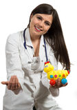 Portrait of young friendly female doctor holding toys. Closeup portrait of friendly, smiling confident female doctor holding toys, healthcare professional Stock Photos