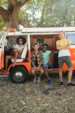 Portrait of young friends with camper van parked at campsite Royalty Free Stock Image