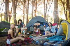 Portrait of young friends holding drinks at campsite Stock Images