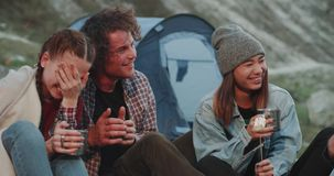 Portrait of young friends multicultural spending a nice time together in the middle of mountain , beside of bonfire
