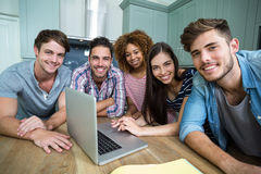 Portrait of young friends smiling while using laptop Stock Photography