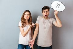 Portrait of a young frustrated couple having an argument. While standing and holding speech bubble over gray wall royalty free stock image