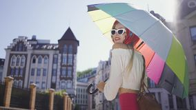 Portrait young fun woman looking at the camera holding multicolored umbrella standing on the street. Attractive. Positive beautiful young woman looking at the stock video