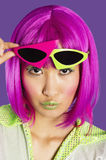 Portrait of young funky woman in pink wig puckering lips over purple background Royalty Free Stock Image