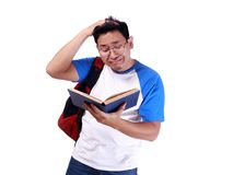 Young Male Student Worried When Reading Exam Report. Portrait of young funny Asian male student stressed or worried when reading book or his exam report Stock Images