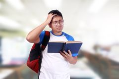 Young Male Student Worried When Reading Exam Report. Portrait of young funny Asian male student stressed or worried when reading book or his exam report Stock Photography