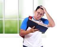 Young Male Student Worried When Reading Exam Report. Portrait of young funny Asian male student stressed or worried when reading book or his exam report Stock Photo