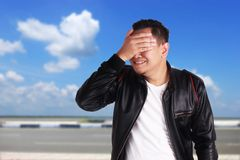 Asian Man Closing His Eyes. Portrait of young funny Asian man wearing black leather jacket closing his eyess as if he is scared to see something bad, ignoring royalty free stock images