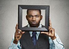 Portrait young funny executive man sticking head in picture fram Royalty Free Stock Photography