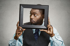 Portrait young funny executive man sticking head in picture fram Royalty Free Stock Photos