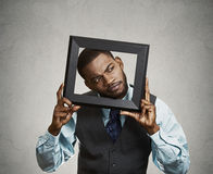 Portrait young funny executive man sticking head in picture fram Royalty Free Stock Photo