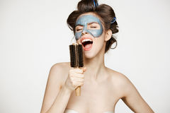 Portrait of young funny girl in hair curlers and facial mask singing in comb over white background. Beauty and skincare. Concept. Copy space Stock Photos