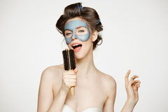 Portrait of young funny girl in hair curlers and facial mask singing in comb over white background. Beauty and skincare. Concept. Copy space Stock Photography