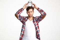 Portrait of a young funny man holding alarm clock royalty free stock photo