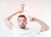 Portrait of young genious man holding lamp. Guy with an idea - isolated with clipping path Royalty Free Stock Photo