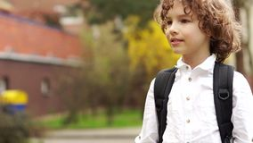 Portrait of a young genius. A schoolboy with a knapsack behind her, looks thoughtfully and seriously into the distance