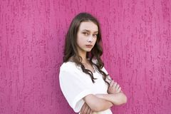 Portrait of young giel with crossed arms. Beautiful young lady with crossed arms looking at camera. Brunette in stylish white dress posing isolated on pink stock photos