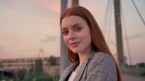 Portrait of young ginger woman in jacket standing on bridge, looking away and then into camera, smiling, sunset.  stock video