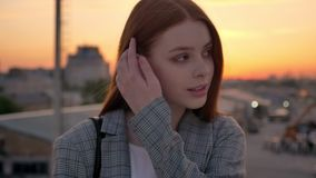 Portrait of young ginger woman in jacket standing on bridge and looking into camera, smiling, industrial factory. Background, sunset stock video