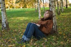 Portrait of a young girl. Thoughtful girl sitting under a tree in autumn forest Royalty Free Stock Images